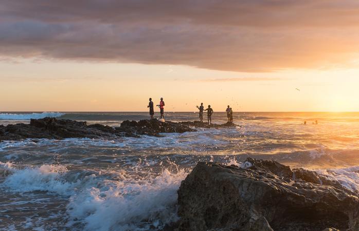 Uma trupe de pescadores tenta apanhar peixes exóticos na frente de praia.