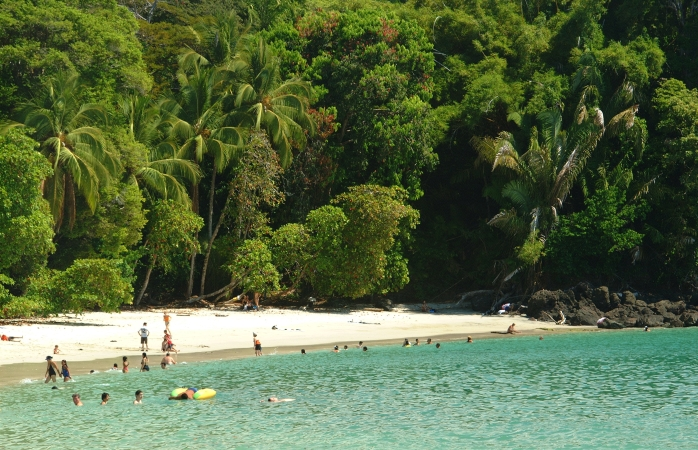 Um pequeno grupo de veraneantes descansa e nada na Praia Manuel Antonio, Costa Rica.