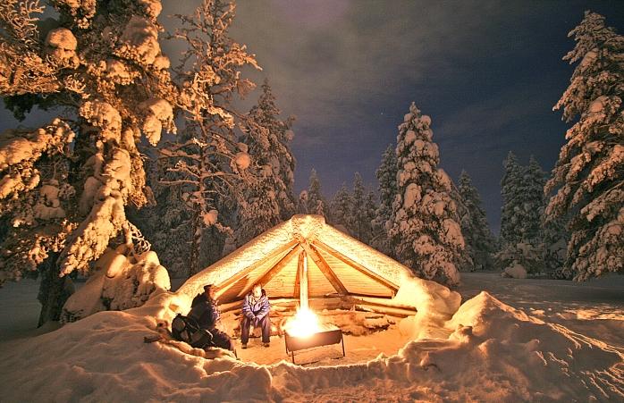 Dois tipos aquecem-se frente à fogueira na floresta durante o Inverno na Finlândia.