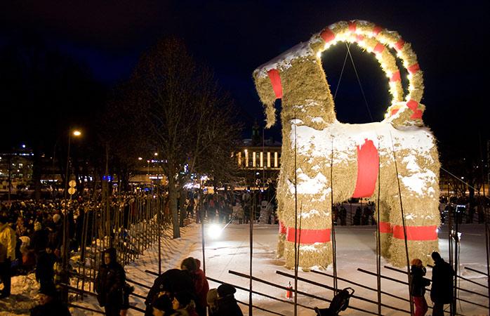 Pessoas a observar a Gävle Goat na Suécia, momentos antes de ser acesa. Uma das tradições de Natal desta região
