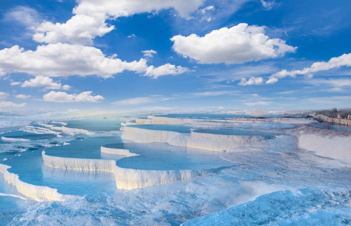 Águas azuis e piscinas brancas fofinhas. Pammukale é como um paraíso de nuvens na terra