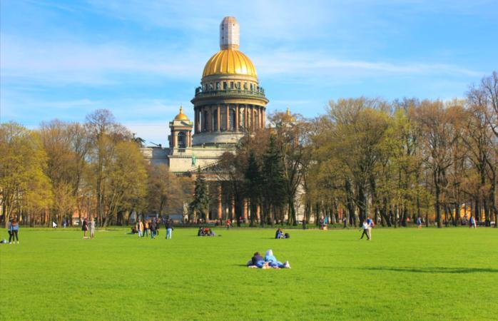 A Catedral de S. Isaac ao fundo, enquanto as pessoas relaxam no parque de S. Petersburgo.