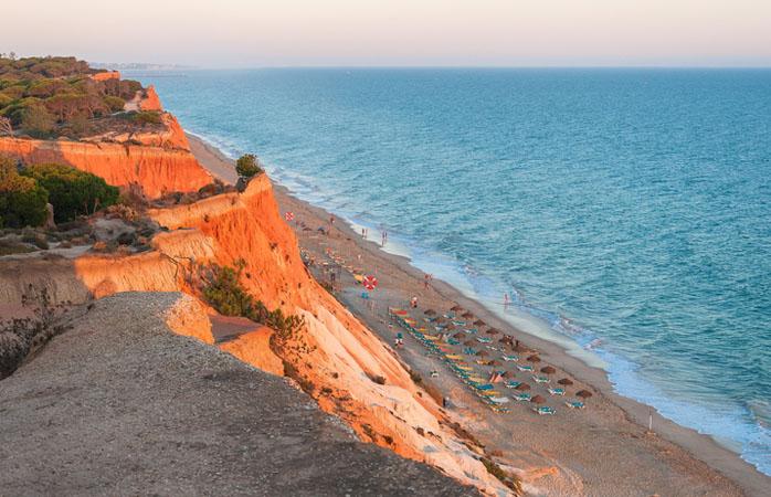 A praia da Falésia é provavelmente um dos cenários mais bonitos de Portugal para assistir ao pôr do sol.