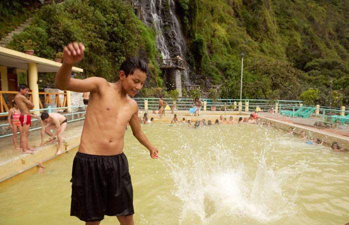 Conversa com os habitantes locais nas termas de Baños, completo com uma vista da cascata