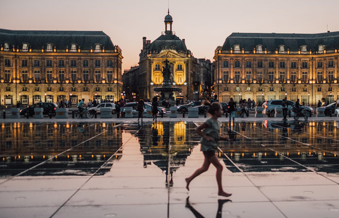 A bonita Place de la Bourse de Bordéus refletida num espelho de água