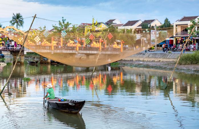 Um homem rema o seu barco de pesca típico em Hoi An, Vietname